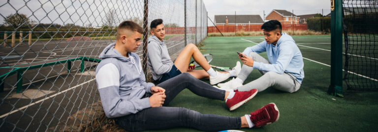 three teenage boys sit down on a tennis court