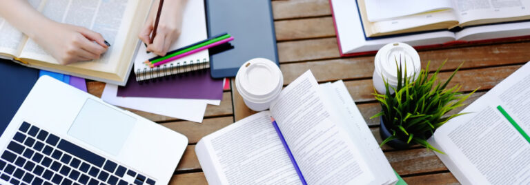 table with coffee cup, books, and laptop