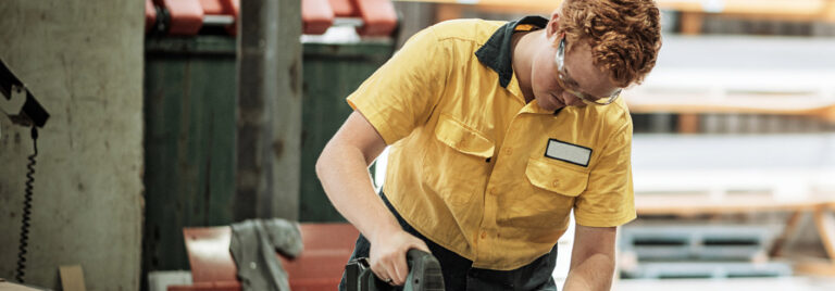 young apprentice using a power tool