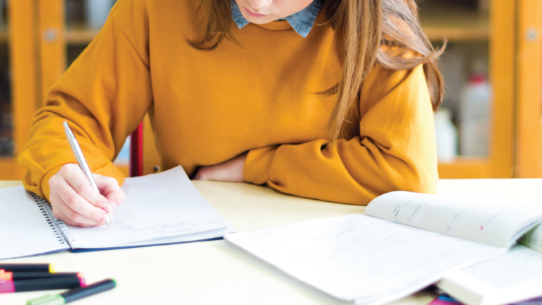 teenage girl writing in an exercise book