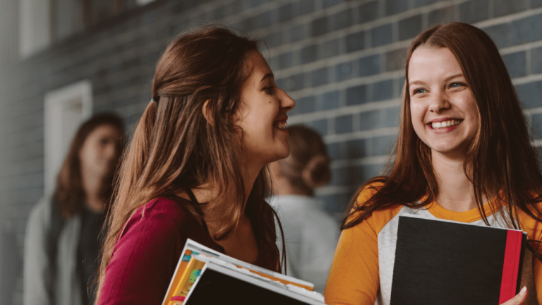 two girls smiling and holding textbooks